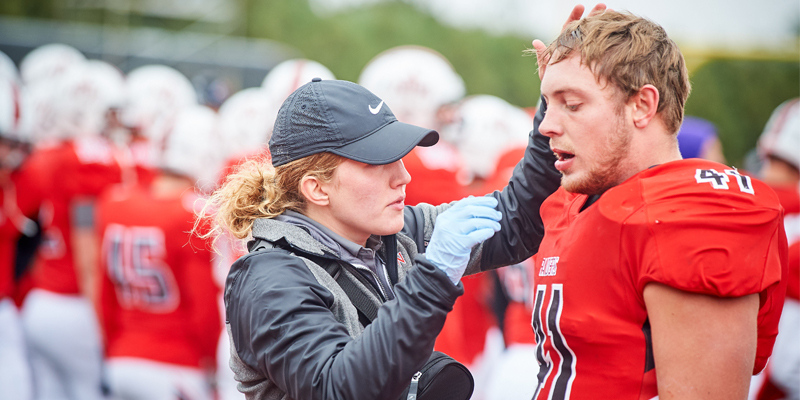 Athletic trainer assisting football player